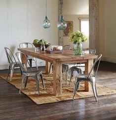 grande table à manger en bois massif avec chaises métalliques et suspensions en verre