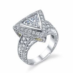 18kt white gold engagement ring featuring a 1.34ct Diamond trillion center stone with .75ct Diamond melees around it and on the shank. There is swirl fili