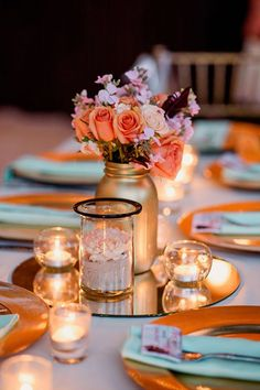 Gold-painted mason jars and candles cast a romantic glow against a mirror.