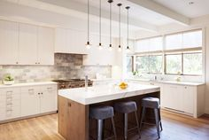 A white and bright kitchen space with tiled backsplash, marble island countertop, black bar stools, and industrial lighting
