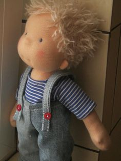 A 38 cm (14 inch) doll made of natural materials, stuffed with pure wool. The doll can be dressed in multiple variations. Its included outfit contains the