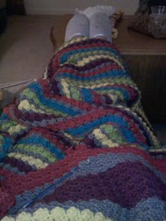 Very large, king sized afghan in the blanket stitch. Colors are gray, yellow, bright green, bright blue, purple, and a bright red. I gave this to Cloe.