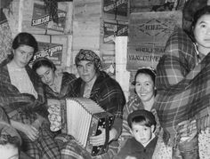 "Black and white photograph of five women, four of them seated and one on the far right standing with a baby wrapped in a plaid shawl. The woman in the centre of the photograph is playing an accordion, and the woman to her left has a young boy in her lap. Behind them are several wooden crates labeled ""Marven's Biscuits"" and one marked ""H.B.C. Wholesale Vancouver."""