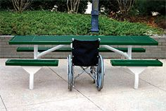 Wheelchair accessible picnic table designed for social interaction.   Featuring a space in the middle of the table instead of at the end, bringing a person who uses a wheelchair closer to their friends and family.