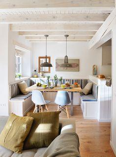 """Para toda la familia. El comedor lo forma una mesa cuadrada rodeada por un banco de obra forrado de madera, en forma de """"U"""". Unas colchonetas lo hacen más cómodo."""