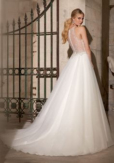 Beadwork and a high neckline give this tulle Bridal Dress a truly unique look. The illusion back is accented by beading and buttons. Colors available: White, Ivory