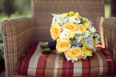 Yellow and blue bouquet of roses, blue thistle, craspedia and dusty miller.
