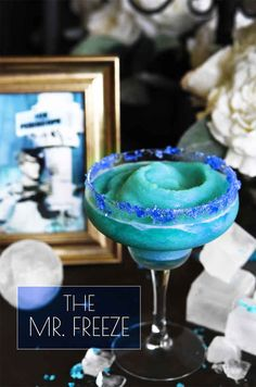"""Batman Cocktails - Mr Freeze Cocktail Recipe -  6 oz. pineapple juice 1.5 oz. white rum 1.5 oz. blue Curaçao 3–4 blue raspberry Jolly Rancher candies (optional) The night before making: Divide pineapple juice between sections of an ice cube tray and freeze until solid.Crush Jolly Rancher candies with kitchen tool. Empty """"crystals"""" onto a small plate. Rub rim with lime slice, roll candy crystals"""
