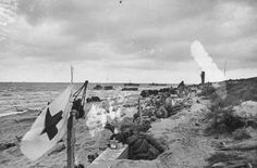 American GIs in beach foxholes on second day after Normandy invasion during WWII; troop carriers visible in water and flag w. cross on it in fore. June 7, 1944. Photographer: Bob Landry