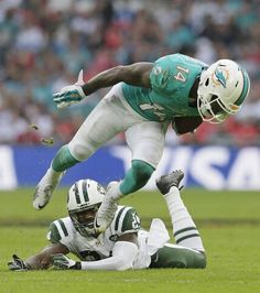Miami Dolphins' Jarvis Landry breaks the challenge from New York Jets' Darrelle Revis during the NFL football game between the New York Jets and the Miami Dolphins and at Wembley stadium in London, Sunday, Oct. 4, 2015.