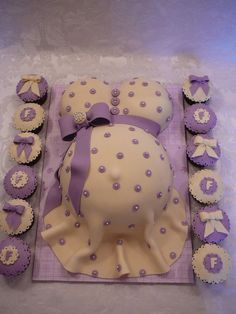 Pregnant Belly A shower pregnant belly cake with jewel on the bow, all edible. This is a vanilla cake with buttercream covered with fondant...