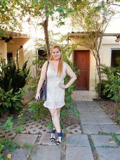 Vestido de tricô bege usado com bolsa saco e sandália pesada azul, deixando o visual menos óbvio.