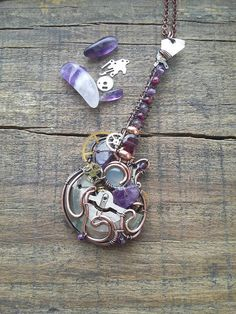 One of my favourite designs of the acoustic guitar. It has a moonstone, amethysts and garnets in it. About 3 inches long. With 17 chain included. Copper is protected with some clear. I ship to any country for $6