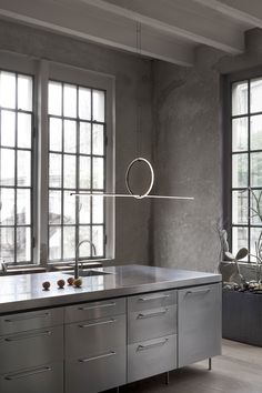 Arrangements, by Michael Anastassiades, is a beautifully bold and modern chandelier. When incorporated into this sleek, minimal kitchen, Arrangements offers a combination of geometric and jewelry-inspired aesthetic. This unique pendant design provides warm illumination above the kitchen counter.   #flos #floslighting #lightingdesign #italiandesign #interiordesign #designinspiration #interiorinspiration #modernlighting #contemporarylighting #pendantlight #kitchenlighting #kitchendesignideas Geometric Pendant Light, Modern Pendant Light, Modern Chandelier, Kitchen Installation, Light Installation, Suspended Lighting, Modern Lighting, Lighting Design, Minimal Kitchen