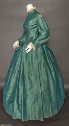 """TEAL WOOL DAY DRESS, 1850s   In the Swan's Shadow TEAL WOOL DAY DRESS, 1850s   2 piece, changeant fine wool, bodice pointed at CF & CB, bishop sleeves, box pleated skirt, brown cotton bodice lining & hem facing, B 34"""", Skirt W 30"""", Bodice W 25"""", Skirt L 41"""", (skirt enlarged & tiny B stain, 1 very tiny moth hole below back neck, 1 very small ink stain & 2 tiny holes at lower skirt, buttons moved, lace trim added 20th C)."""