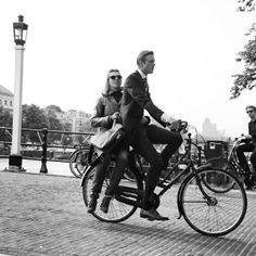 Daily life in Amsterdam; cycling together on one bike to work #commute #cyclechic #Amsterdam #amstel #skinnybridge #suits #stylish #sunglass...