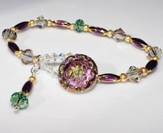 Beautiful shades of purple and green can be seen in this button clasp bracelet. The button is a Czech created vintage reproduction. The clasp is also created with Swarovski crystals. Erinite, and Purple Haze crystals are scattered through this bracelet, which will fit up to a 7 1/4 inch bracelet. $84