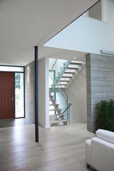 stone inside entry and wood the rest of the way and down the hall. nice stairs too House on the Bluffs by Taylor Smyth Architects