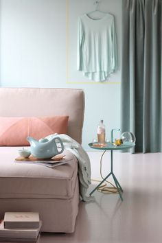 pastels.  cushion with geometric stitching and yellow rubber cord lamp from Hay. Teapot from Norway Designs.