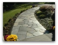An attractive flagstone walkway with a nice gentle curve from the house to the driveway. Notice the width is wide enough for two people to  easily pass one another.