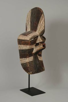 A Songye Kifwebe Mask, Democratic Republic of Congo,     of typical form, the square chin set under a projecting mouth, the triangular nose set under a high crested coiffure, pierced elongated eyes,  the surface incised with horizontal grooves and decorated with white, black and red pigments, pierced around the edges for attachment, with stand  Size:     Height: 56 cm