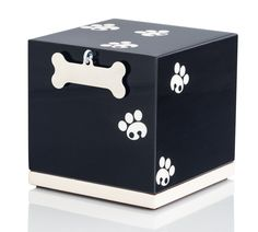 This unique dog urn features natural white paw prints on black lacquered wood. The charm attached charm can be engraved. Free shipping & returns.