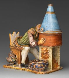 "metmuseumIn this maiolica sculpture, a man leans forward in his seat with his head in a covered pot set above a fiery hearth. The man's actions are explained by an inscription on the chair: ""I distill my brain and am totally happy."" The exhibition ""Renaissance Maiolica: Painted Pottery for Shelf and Table,"" on view in gallery 521, celebrates the publication of ""Maiolica, Italian Renaissance Ceramics in The Metropolitan Museum of Art"" by Timothy Wilson. Inkstand with A Madman Distilling His…"