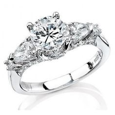 This gorgeous Natalie K 18k white gold three stone engagement ring setting, contains pear shape and round brilliant cut white diamonds of G color, VS2 clarity, excellent cut and brilliance.