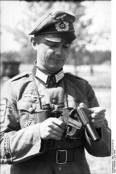 """An officer of the """"Großdeutschland"""" Division loads a Kampfpistole near Achtyrka, Ukraine, June 1943. He has been awarded the Deutsches Kreuz in Gold (cloth version) and 4 Panzervernichtungabzeichen."""