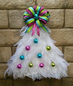 This Sweet Christmas Tree shaped wreath would brighten anyones Holiday Decor. It is white with colored balls and a matching glittery bow. It would be perfect for someone who is in a nursing facility over the holidays to add a festive look to their room. It is made from Deco Mesh and