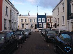 Foto de uma rua em Notting Hill. Casinhas coloridas, mas em tons terrosos. Um senhor na porta de casa abrindo o guarda-chuva.