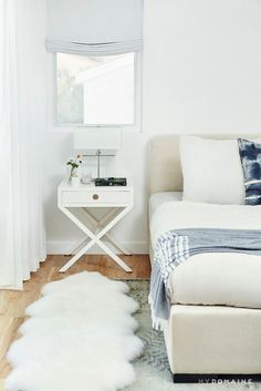Bright, minimal, and contemporary bedroom with a cream headboard, a small white nightstand, and layered area rugs