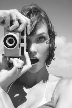 Karlie Kloss with camera. Behind camera, woman, female, clouds, rings, hands, focus, mouth, eyes, surprise, photograph, photo b/w.