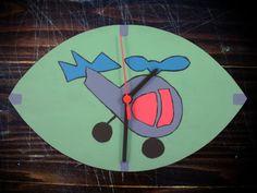 Açıklama: Helikopter desenli boyama. Teknik: Ahşap boyama. Malzeme: Parke. İşlemler: Eliptik kesim ve mat vernik. Saat tipi: Sessiz akar saat. Bütün ölçü: 29,5 cm en, 18 cm boy.