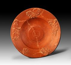 Roman terra sigillata plate with applied decor, African red slip ware, 4th - 5th century A.D. Chi Rho over lamp, bearded man (Saint Peter?), youth with wreath (Christ?) and below an Eros with torches and vases, 20,8 cm diameter. Private collection