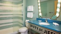 A toilet flanked by a sink with 'Spiffy in a Jiffy' written below it and a glassed-in shower