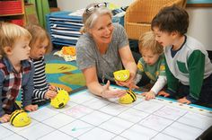 Cook preschool teacher Lisa Dickinson engages three-year-olds in a directional programming activity