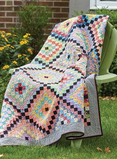 VINTAGE CHARM by Carmen Geddes: Grandmother's lovingly-made granny-square afghan inspired Carmen Geddes to create a quilt of a similar layout. All of the squares in the quilt finish at 1″ square, sized in the tradition of a postage-stamp quilt. It's in the layout of the colorful squares that the granny squares take shape.