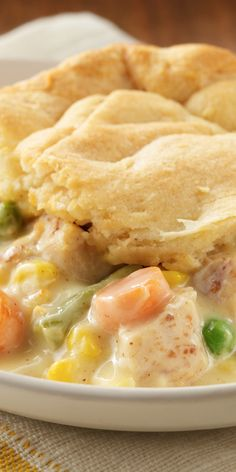 A hearty recipe with tender chunks of chicken and vegetables in a creamy sauce with a flaky topper .