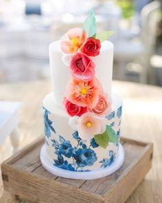 A small salted-caramel cake, from Hey There Cupcake boasted a blue hand-painted exterior and shades of orange paper flower garnishes.