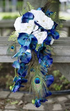 Cascading Blue and White Peacock and Orchid Bouquet Idea Cascading bouquets are coming back in style, and this one makes a gorgeous statement. We started with 2 of the blue orchid stems, 1 open sophia white rose, and 4 open white roses for the flowers. We also included peacock feathers and some greenery from the button fern bush.