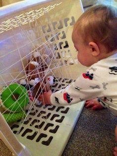 Je neemt een wasmand met allemaal draden en dan interessant speelgoed erin het beweegkind moet de voorwerpen proberen nemen