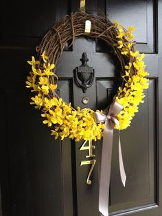 DIY Spring Wreath: grapevine wreath with forsythia stems and a gray bow
