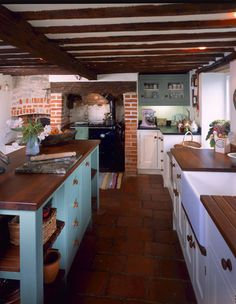 Cottage kitchen with terracotta floor.  Dark work wood surfaces.  The ceiling and back splashes on the wall in the back make this amazing