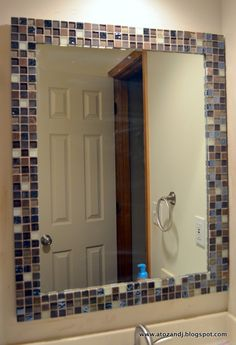 Use mini tiles to match the shower tiles around a think flat frame on a big mirror paint the bathroom walls taupe, take the medicine cabinets down, add shelves above the toilet