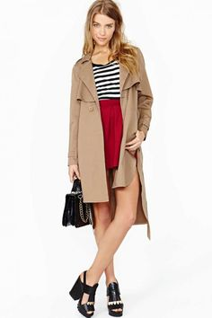 Totally essential khaki trench coat featuring a rounded, asymmetric hem and layered panel at chest. Side pockets, tie waist. Unlined, double button closure. Split at sides, button tabs at shoulders.