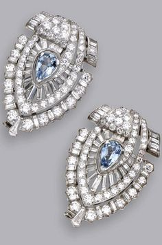PAIR OF DIAMOND AND AQUAMARINE CLIP-BROOCHES, CIRCA 1935 Of modified openwork shield-shape, set with 2 pear-shaped aquamarines weighing approximately 2.40 carats, accented by 120 round and 76 baguette and tapered baguette diamonds weighing approximately 9.80 carats, mounted in platinum.