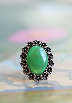 """Around The Rosie Ring 9.99 at shopruche.com. A green stone with gold undertones adds the perfect pop of color to this floral designed brass ring. Adjustable band.  1.5"""" tall"""