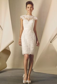 Brides: Alfred Angelo. Re-embroidered lace natural waist gown with a sheer lace cap sleeve and illusion neckline, sweetheart neckline, key hole back, satin belted waist, and fitted pencil skirt with back vent.