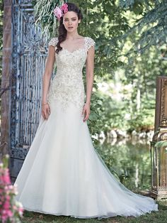 Maggie Sottero - LADONNA, Elegant and sophisticated, this A-line wedding dress combines a decadent, Swarovski crystal beaded lace bodice with an ethereal Chic organza and tulle skirt, perfect for the truly romantic bride. Finished with sweetheart neckline and corset closure. Detachable beaded lace cap-sleeves sold separately.
